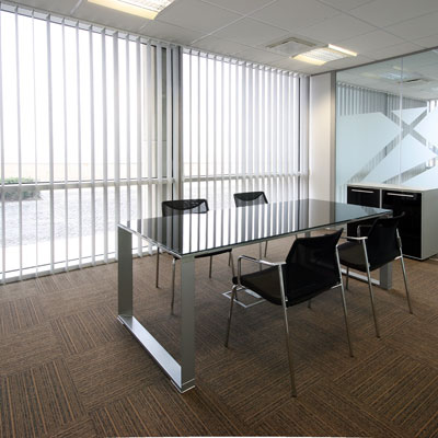 Bright conference room office space with white vertical blinds