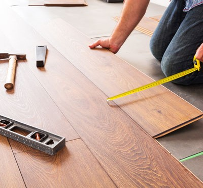 contractor on his knees installing hardwood floor while using measuring tape