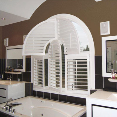 Bright modern bathroom with uniquely shaped white wood shutters