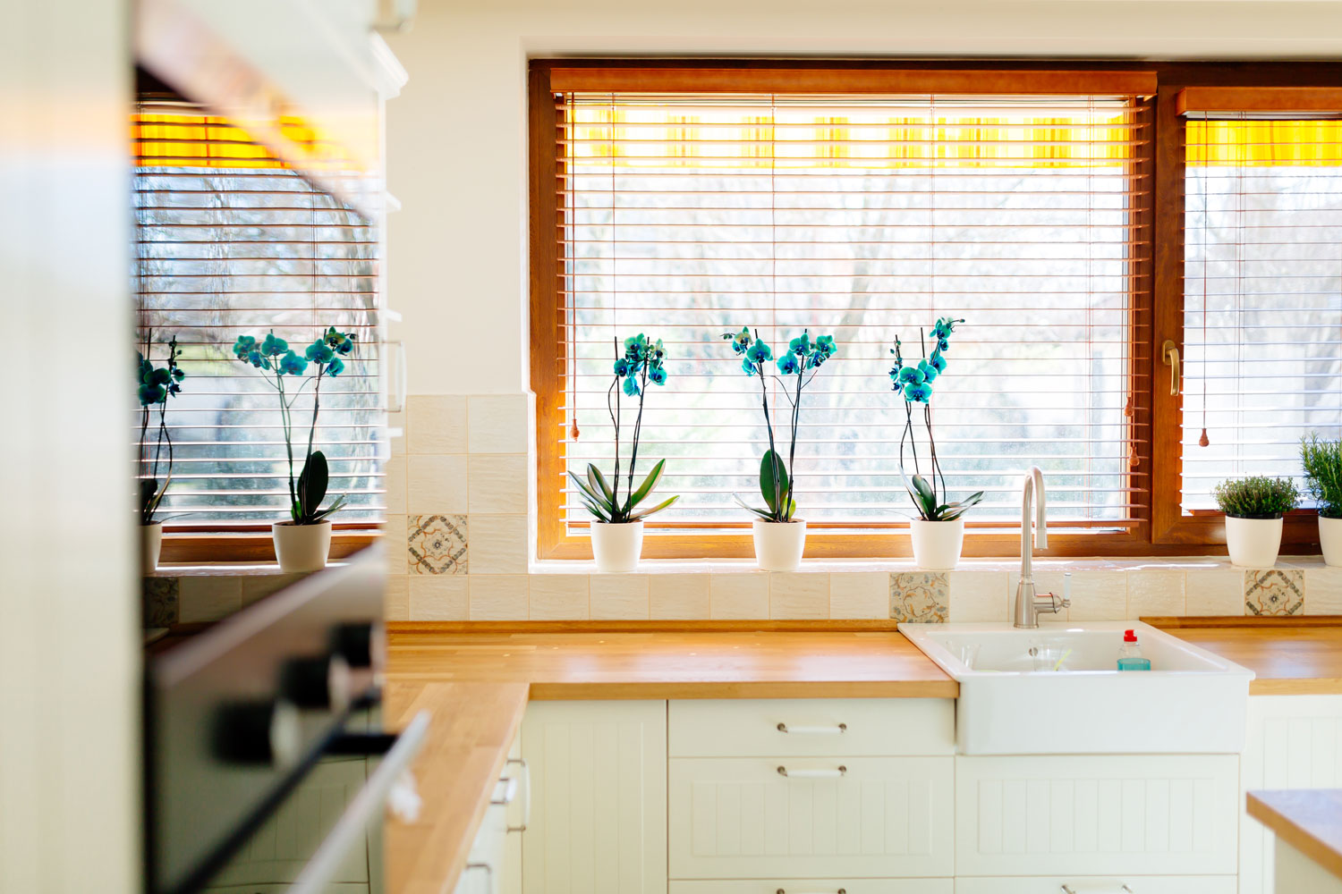 A bright modern kitchen with warm orange colour blinds and overlooking the frontyard