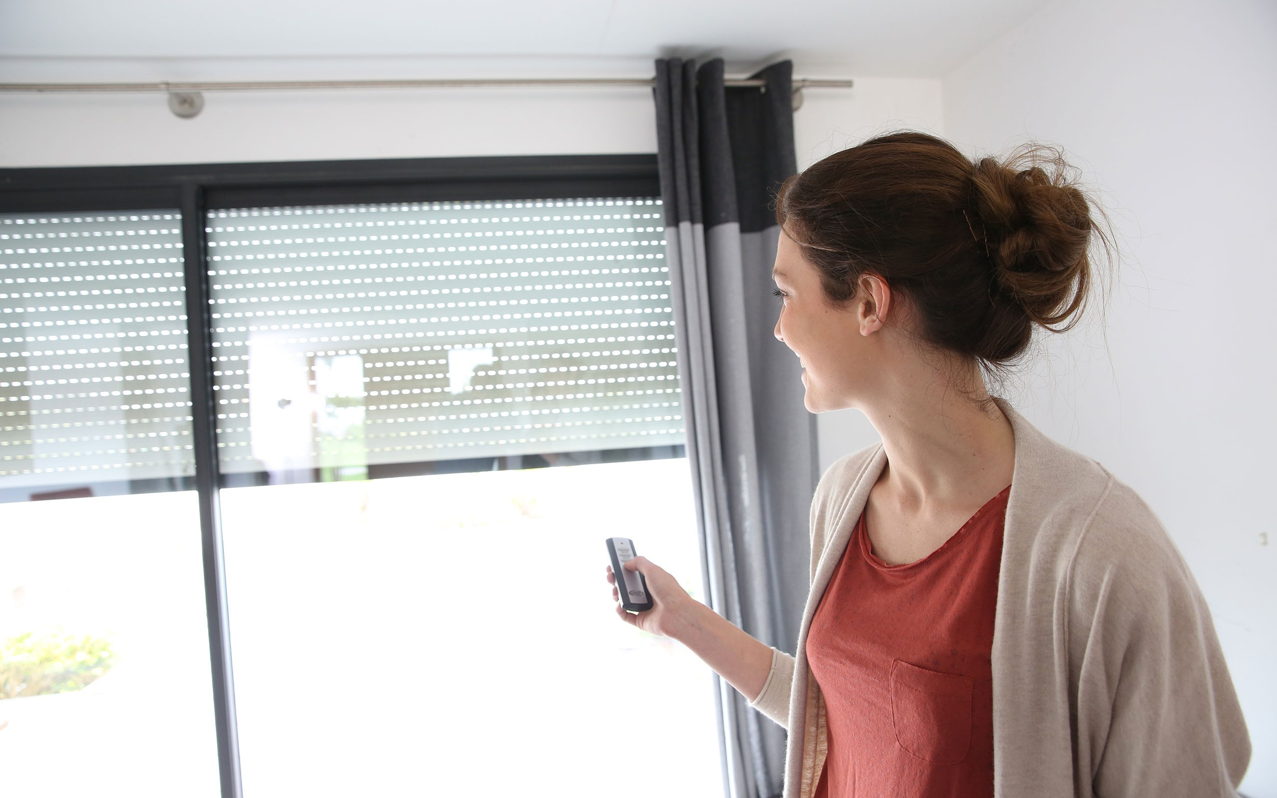a smiling woman in a red shirt trying a motorized blind at home with remote control