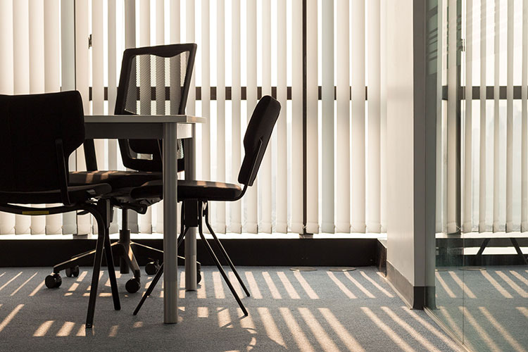 Bright conference room office space with sun streaming in through vertical white blinds