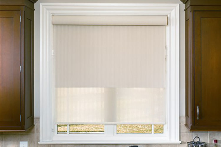 A light beige double roller shade is installed on kitchen window