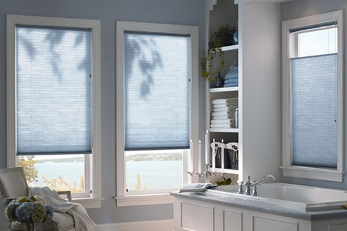 A bright bathroom interior overlooking the ocean with horizontal light blue honeycomb cellular shades